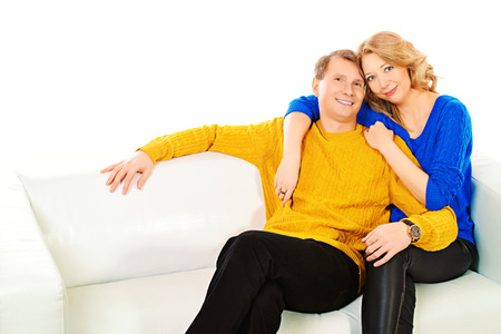 Portrait of a happy elderly couple sitting on sofa and smiling at camera. Isolated over white. photo