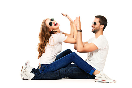 Happy emotional young couple in love posing at studio. Isolated over white. photo