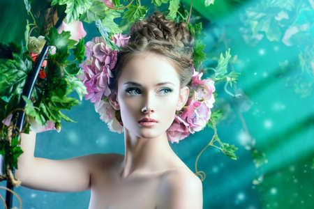 Beautiful young woman standing under an arch of flowers and overgrown loach. Magic of the spring. Stock Photo - 27586175