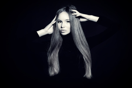 magnificent: Beautiful girl with magnificent long hair posing over black background. Black-and-white photo. Stock Photo