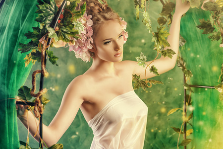 Beautiful young woman standing under an arch of flowers and overgrown loach. Magic of the spring. Stock Photo - 27586183