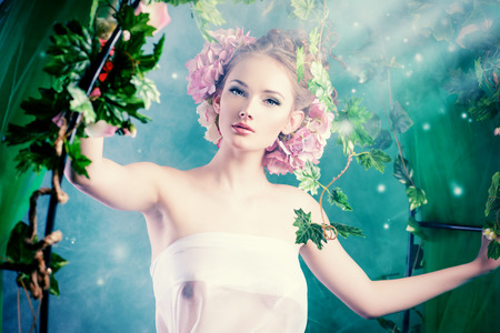 Beautiful young woman standing under an arch of flowers and overgrown loach. Magic of the spring. Stock Photo - 27586186