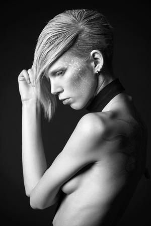 Fashion photo of an extravagant model over black background.Black-and-white photo. Stock Photo