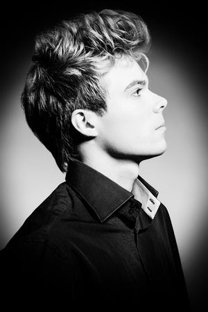 Portrait of a handsome young man posing at studio. Profile. photo