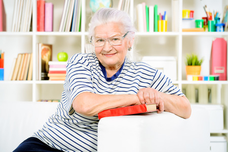 Smiling senior woman sitting at home on a sofa and reading a book. photo