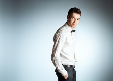 Handsome young man in elegant white shirt and bow tie. Studio shot. photo