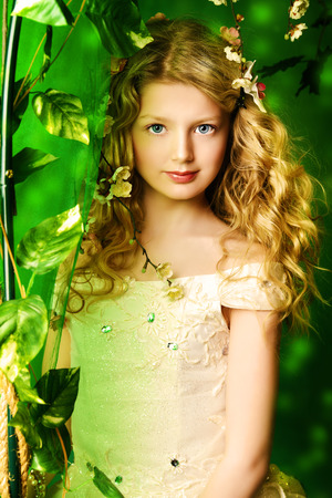 garden eel: Lovely girl in a lush white dress stands under a floral arch over green .