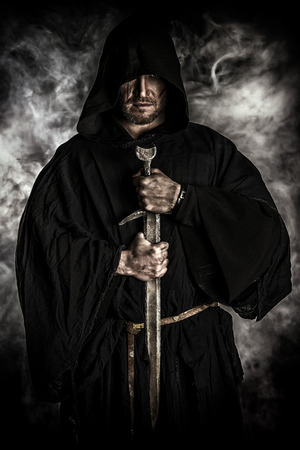 ancient warrior: Portrait of a courageous warrior wanderer in a black cloak and sword in hand. Historical fantasy.