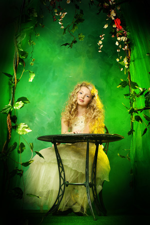 Lovely girl in a lush white dress sitting at the table under a floral arch over green .