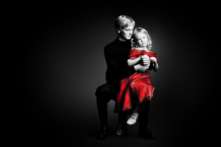 Portrait of an elder brother and his little sister over black background. photo