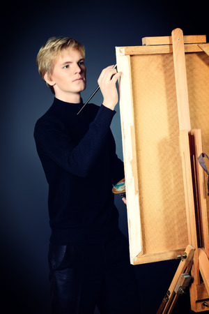 Young man artist paints on canvas with oil paints. Studio shot over black background. photo