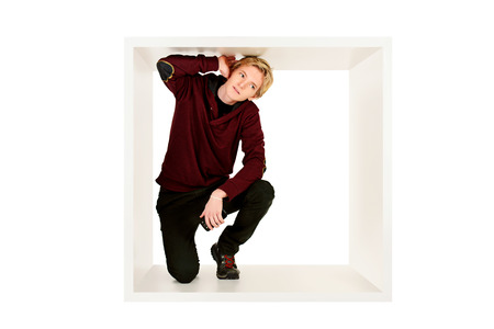 restrictions: Young man in casual clothes sitting in white cube and listens. Concept of rules and restrictions. Isolated over white.
