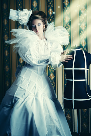 Beautiful fashion model in the refined white dress and mannequin  Vintage style  Art project  Haute Couture  photo