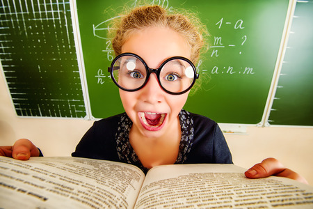 Funny schoolgirl in big round glasses opened the book and shouting at camera. Education. photo
