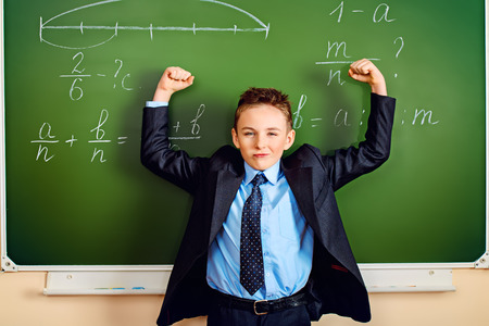 Happy schoolboy stands at the blackboard in the classroom and raised his hands with joy. Education. photo