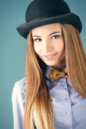 Elegant girl model poses in blouse, bow tie and bowler hat. Refined style of old Europe. photo