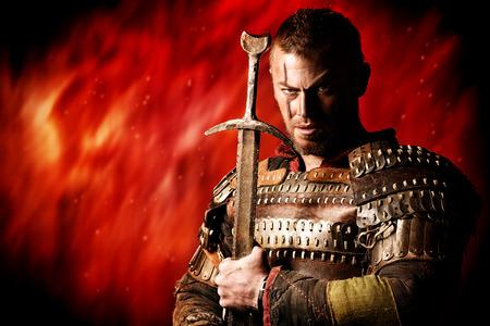 guerrero: Retrato de un antiguo guerrero valiente en armadura con la espada. Foto de archivo