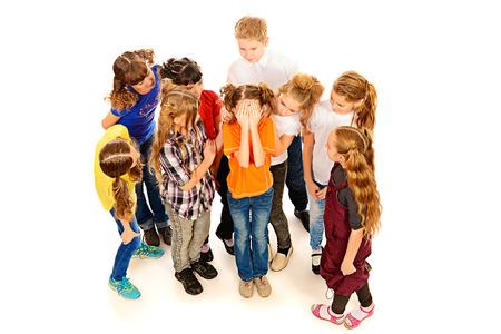 Children stand around crying girl. Isolated over white. photo