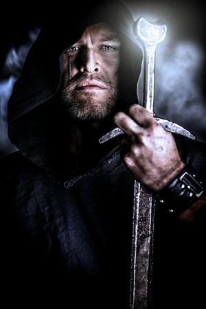 cavaliere medievale: Ritratto di un vagabondo guerriero coraggioso in un mantello nero e la spada in mano. Fantasy storico.