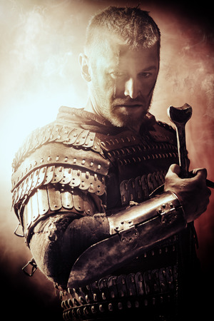 Portrait of a courageous ancient warrior in armor with sword.