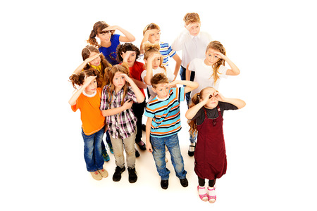 Group of cheerful schoolchildren standing together and facing the same direction. Isolated over white. photo