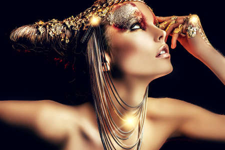 fantasy woman: Art project: beautiful woman with golden make-up. Jewelry, make-up. Fashion. Over black background.