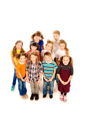 Grupo de escolares alegres de pie juntos. Aislado en blanco. photo