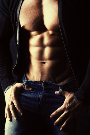 Sexual muscular young man over dark background.  Male torso, abdominals. photo