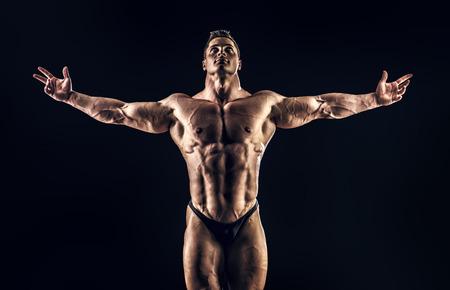 culturista: Culturista musculoso guapo posando sobre fondo negro. Gloria del campeón.