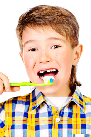 Little funny boy smiling and brushing his teeth. Healthcare. Isolated over white. photo