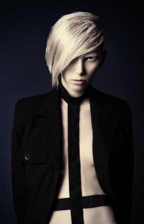 butch: Portrait of an extravagant seductive model with boyish make-up and haircut. Black background.  Stock Photo