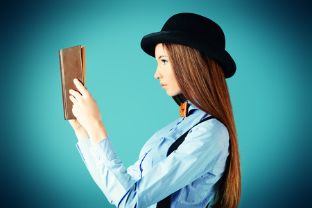 Elegant girl model in blouse, bow tie and bowler hat reading a book. Refined style of old Europe. photo