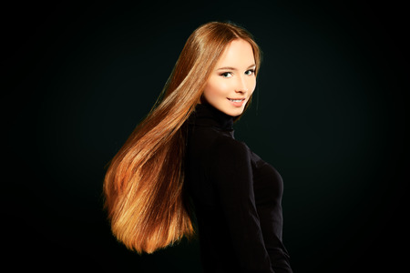 magnificent: Happy beautiful girl with magnificent long hair in motion posing over black background.