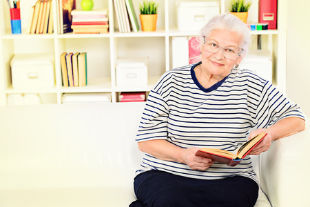 wise woman: Smiling senior woman sitting at home on a sofa and reading a book.