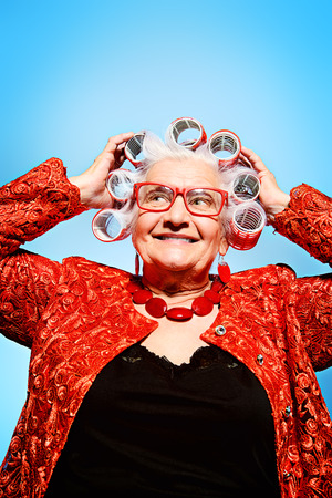 Portrait of an elderly woman in curlers looking at camera. photo