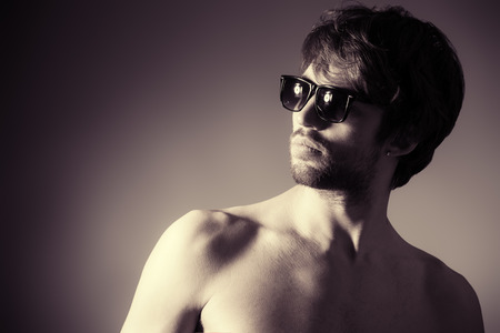Handsome shirtless young man posing at studio. Black-and-white. photo