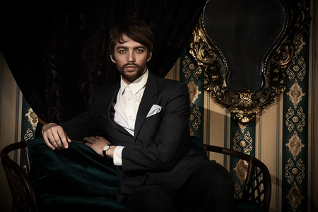the seducer: Handsome man in elegant black suit posing in the classical vintage interior. Stock Photo