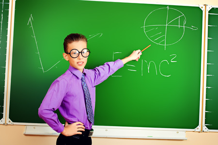 Smart schoolboy stands at the blackboard in the classroom. Education. photo