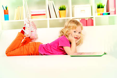 play room: Cute little girl lying on a sofa at home and reading a book. Stock Photo