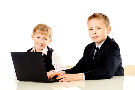 kids laptop: Two schoolboys do their lessons together at the table. Isolated over white. Stock Photo