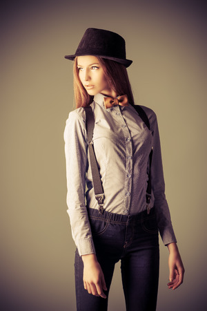 hair tie: Elegant girl model poses in blouse, bow tie and bowler hat. Refined style of old Europe.