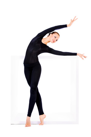 woman black background: Modern bellet dancer posing with a cube at studio. Plastic body concept. Isolated over white.