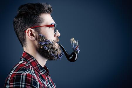 hombre fumando puro: Apuesto joven con gafas y una barba de flores de fumar una pipa. Perfil retrato. Foto de archivo