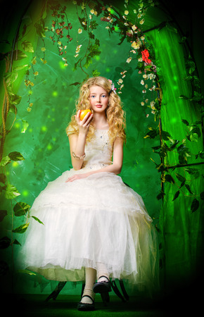 garden eel: Lovely girl in a lush white dress sitting at the table under a floral arch over green background.
