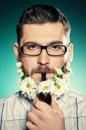 hombre fumando puro: Apuesto joven con gafas y una barba de flores de fumar una pipa.