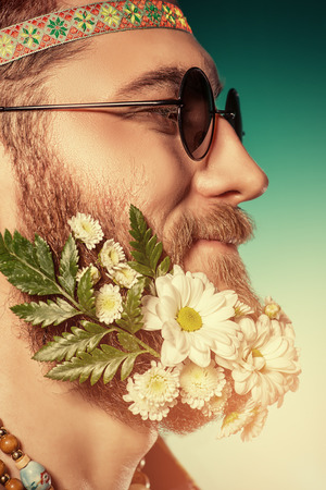 Funny smiling young man in glasses and a beard of flowers. Hippie style.  photo