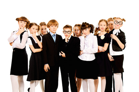 Group of schoolchildren standing together and thinking about something. Isolated over white. photo