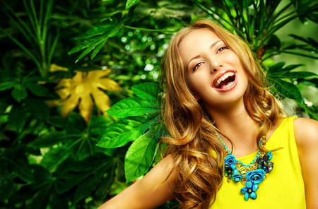 Beautiful laughing young woman among the tropical plants. Vacation. Tropics. Fashion shot. photo