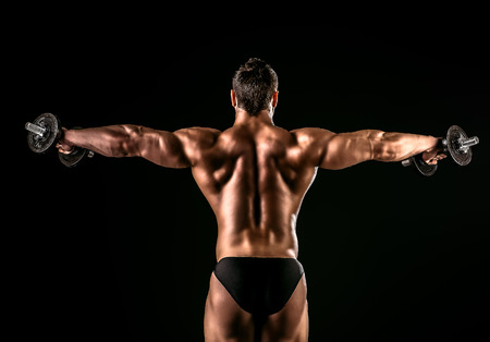 dorsi: Beautiful muscular man bodybuilder posing back over dark background. Stock Photo