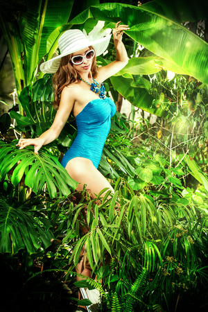 Beautiful young woman in swimsuit stands among the tropical plants. Vacation. Tropics. photo